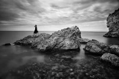 the girl is standing on the rock in the sea