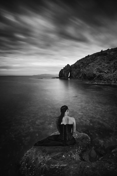 the sad girl is sitting on the rock near the sea