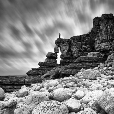 lonely sad man standing over the rocks