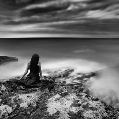 longexposure shot of girl sitting on the rock