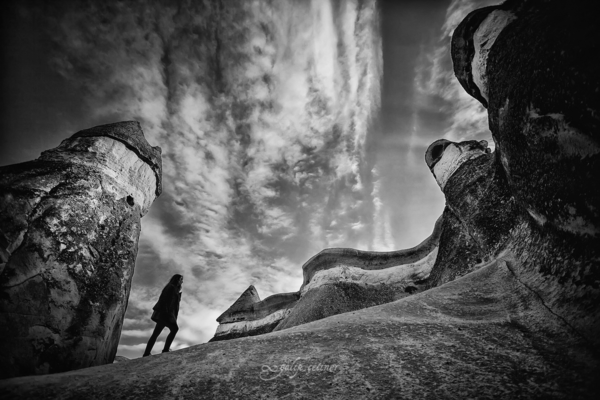 the silhouette of the girl surrounded by the rock formations