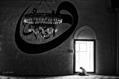 the silhouette of the praying woman in the mosque