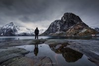 man is staring to the dark heaven in hamnoy, lofoten, norway
