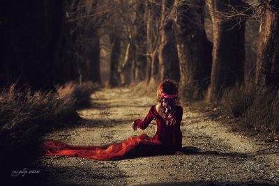 the beautiful girl with a red dress is sitting between the trees