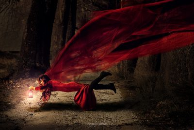 the beautiful girl with a red dress is levitating between the trees