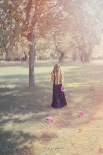 the girl with a black dress is leaving between the trees