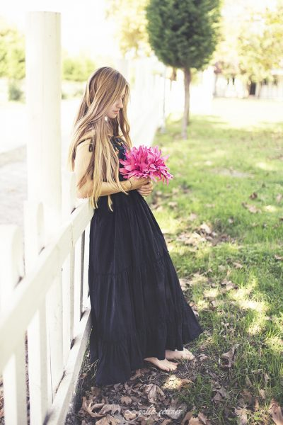 the girl with a black dress is standing in front of the fence