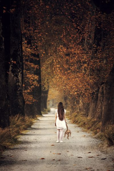 the girl with a toy is walking between the trees