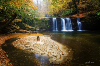 the beautiful girl with a pale dress is sitting in front of the waterfall