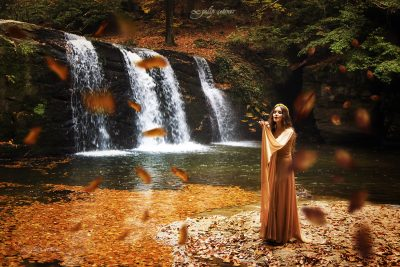 the beautiful girl with a pale dress is blowing the leaves in front of the waterfall