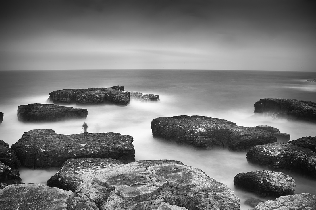 photographer on the rocks in the sea