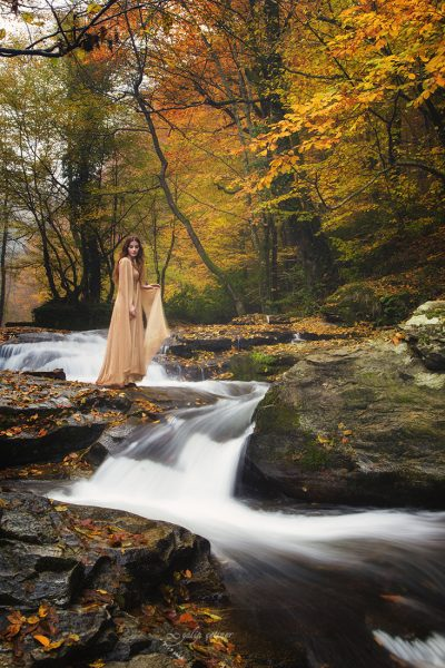 the beautiful girl with a pale dress is standing in front of the waterfall