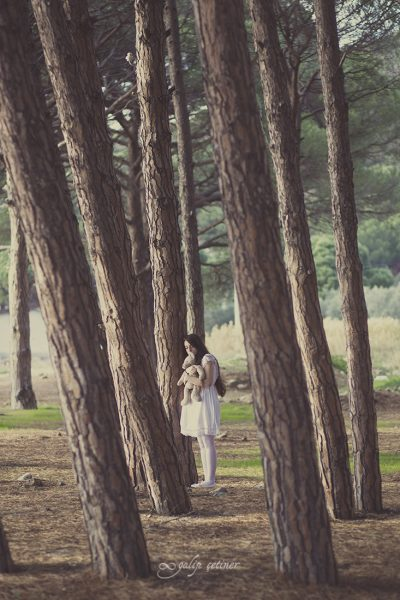 the girl with a toy is standing between the trees