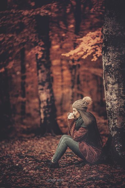 the beautiful girl is drinking the coffee in autumn