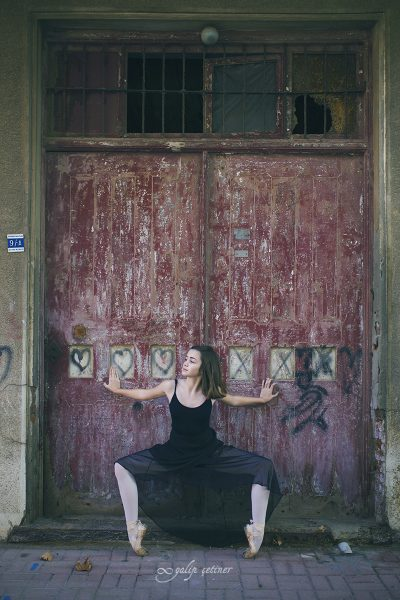 black dressed ballerina girl is on her pointes in front of the old door