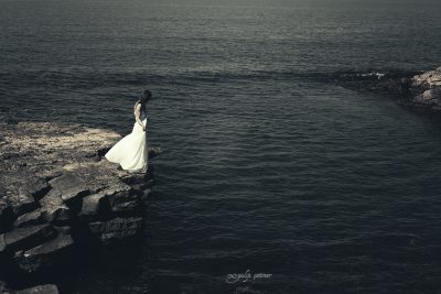the girl with a white dress is standing on the edge of the rock
