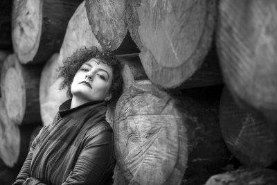 woman portrait besides the logs