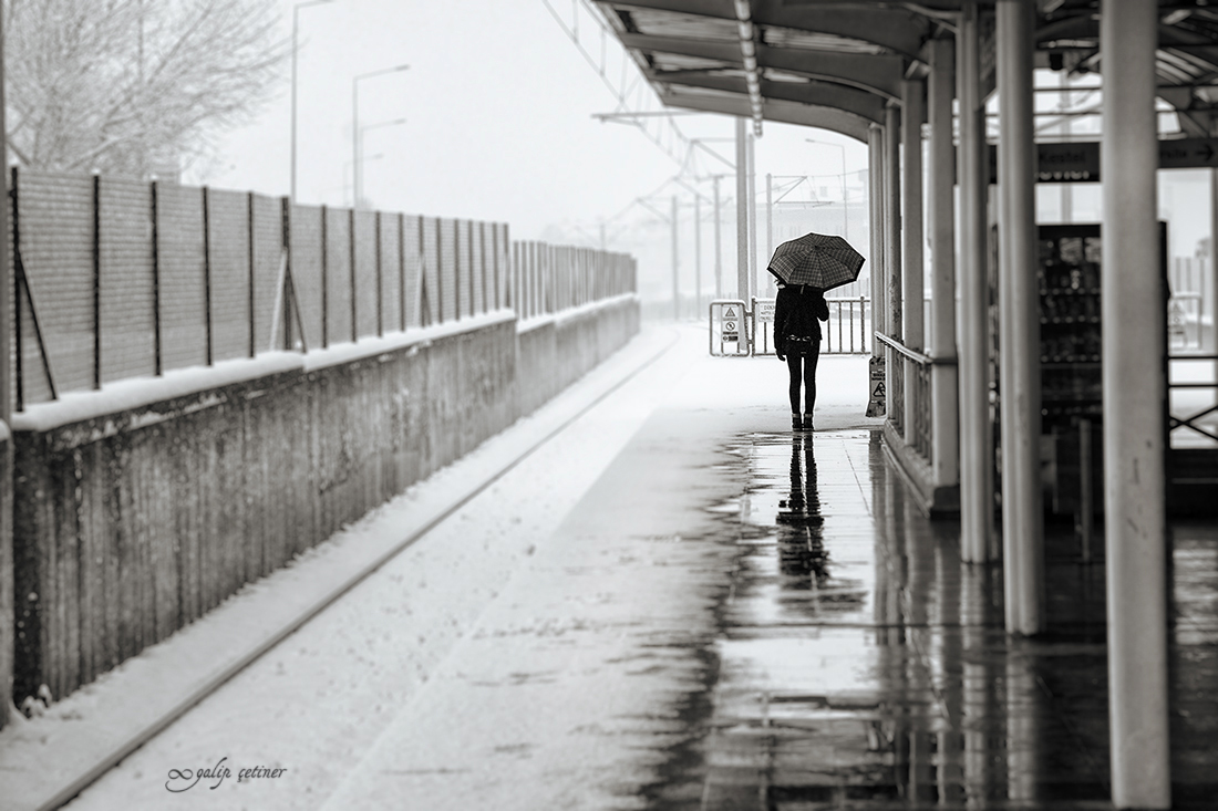 the girl with the umbrella is waiting for the train in the station