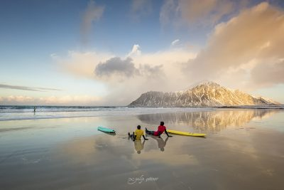 arctic surfers in Skagsanden beach, Lofoten, Norway