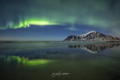 northern lights with reflections in skagsanden, lofoten, norway