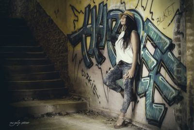 the portrait of the rebel girl standing in front of the graffiti wall