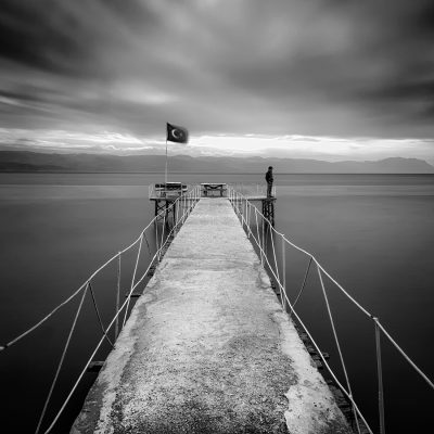the solitary man standing on the pier in longexposure