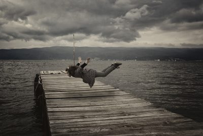 the girl is levitating over the pier