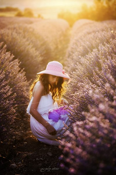 the beautiful girl with a hat is looking to the flowers in the lavender field
