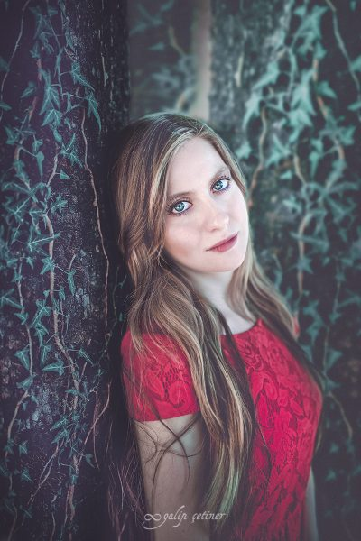 the beautiful girl with a red dress is standing in front of the ivy tree